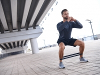 Young sportive man uses resistance band for exercising outdoors