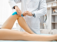 Therapist applying kinesio tape on a woman's knee